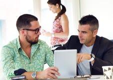Ejecutivos casuales que trabajan junto en una reunión con la etiqueta digital Fotos de archivo libres de regalías