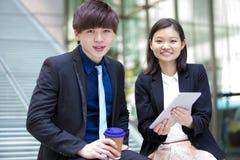 Ejecutivos de operaciones asiáticos jovenes que caminan y que discuten con la tableta Imágenes de archivo libres de regalías