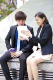 Ejecutivos de operaciones asiáticos jovenes que caminan y que discuten con la tableta Fotos de archivo