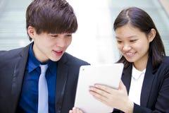 Ejecutivos de operaciones asiáticos jovenes que caminan y que discuten con la tableta Fotos de archivo libres de regalías