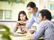 Ejecutivos de operaciones asiáticos que trabajan junto en oficina