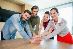 Ejecutivos de operaciones con sus manos apiladas en la tabla de madera en la oficina Foto de archivo