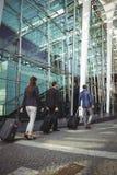 Ejecutivos de operaciones que caminan con la maleta fuera de la plataforma Imagenes de archivo
