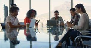 Ejecutivos de operaciones que se sientan en la tabla y que trabajan en la oficina moderna 4k almacen de video