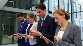 Ejecutivos de operaciones que usan el teléfono móvil y la tableta digital en pasillo metrajes