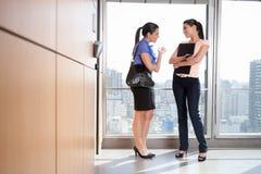 Ejecutivos de sexo femenino que hablan el uno al otro en oficina Fotos de archivo libres de regalías