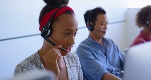 Ejecutivos de ventas bonitos del cliente de la raza mixta que hablan en las auriculares en la oficina moderna 4k metrajes