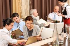 Ejecutivos del almuerzo de asunto que miran el restaurante del menú Foto de archivo libre de regalías