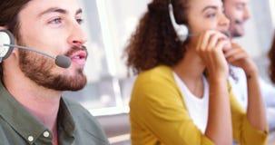 Ejecutivos del servicio de atención al cliente que hablan en las auriculares almacen de metraje de vídeo
