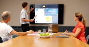Ejecutivos que discuten sobre la pantalla del lcd en la sala de conferencias 4k almacen de metraje de vídeo