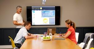 Ejecutivos que discuten sobre la pantalla del lcd en la sala de conferencias 4k almacen de video