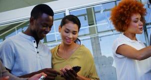 Ejecutivos que discuten sobre la tableta digital y el teléfono móvil almacen de metraje de vídeo