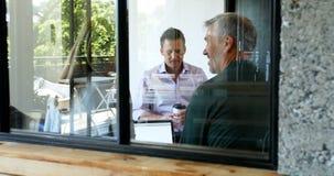 Ejecutivos que hablan el uno al otro en la oficina 4k almacen de metraje de vídeo