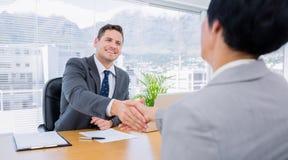 Ejecutivos que sacuden las manos después de una reunión de negocios imagen de archivo