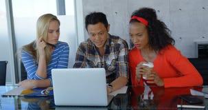 Ejecutivos que se sientan en la tabla y que trabajan en el ordenador portátil en la oficina moderna 4k almacen de metraje de vídeo
