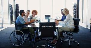 Ejecutivos que tienen discusión en la reunión en la oficina almacen de video