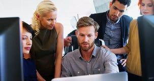 Ejecutivos que trabajan junto en el escritorio almacen de metraje de vídeo