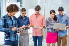 Ejecutivos que usan el ordenador portátil, la tableta digital y el teléfono móvil Imagen de archivo