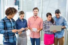 Ejecutivos que usan el ordenador portátil, la tableta digital y el teléfono móvil Foto de archivo libre de regalías