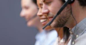 Ejecutivos sonrientes del servicio de atención al cliente que hablan en las auriculares en el escritorio 4k