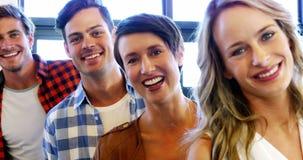 Ejecutivos sonrientes que se colocan en oficina almacen de video
