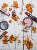 Ejemplo de la foto de las cualidades de la señora Las flores anaranjadas, se ruborizan, lápiz labial y sombra de ojos en un fondo Fotografía de archivo