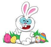 Conejito de pascua que sonríe con los huevos de Pascua Imagen de archivo