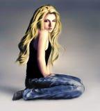 Ejemplo de la muchacha que se sienta en el piso en vaqueros imagen de archivo libre de regalías