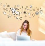 Ejemplo de Rocket con la mujer que usa el ordenador portátil imagen de archivo