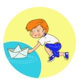 Ejemplo de un muchacho que empuja un barco de papel abajo de un río Fotografía de archivo