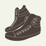 Ejemplo de zapatillas de deporte marrones en fondo beige Fotografía de archivo libre de regalías