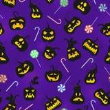 Ejemplo inconsútil en el tema de Halloween, calabazas con las caras y dulces en un fondo púrpura oscuro Fotografía de archivo libre de regalías