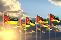 Ejemplo maravilloso de la bandera 3d del día del himno - muchas banderas de Mozambique en la puesta del sol puesta en fila con el ilustración del vector