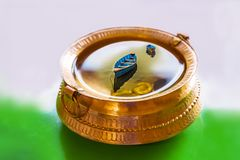 Ejemplo, pote de cobre amarillo con lleno de agua y monedas, barcos coloridos dentro del agua fotos de archivo