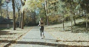 Ejercicio activo joven del atleta de sexo femenino al aire libre en el otoño soleado almacen de video