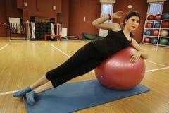 Ejercicio adolescente de la muchacha con la bola del poder en gimnasio Imagenes de archivo