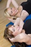 Ejercicio aerobio de la mujer joven dos en una gimnasia fotos de archivo