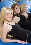 Ejercicio aerobio de la mujer joven tres en una gimnasia foto de archivo libre de regalías