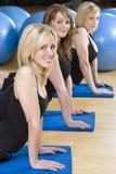 Ejercicio aerobio de la mujer joven tres en una gimnasia fotos de archivo