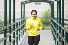 Ejercicio asiático joven de la mujer al aire libre en la chaqueta de neón amarilla, activando Imagen de archivo