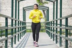 Ejercicio asiático joven de la mujer al aire libre en la chaqueta de neón amarilla, activando Imagenes de archivo