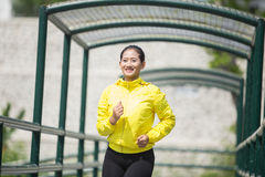 Ejercicio asiático joven de la mujer al aire libre en la chaqueta de neón amarilla, activando Imágenes de archivo libres de regalías