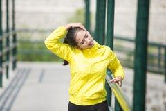 Ejercicio asiático joven de la mujer al aire libre en la chaqueta de neón amarilla, estirando Fotos de archivo libres de regalías