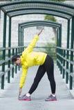 Ejercicio asiático joven de la mujer al aire libre en la chaqueta de neón amarilla, stre Fotografía de archivo