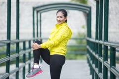 Ejercicio asiático joven de la mujer al aire libre en la chaqueta de neón amarilla, stre Fotografía de archivo libre de regalías