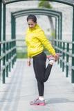Ejercicio asiático joven de la mujer al aire libre en la chaqueta de neón amarilla, stre Fotos de archivo libres de regalías