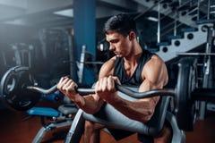 Ejercicio bronceado del hombre con el barbell en gimnasio fotos de archivo