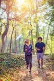Ejercicio cardiio - par que goza en una forma de vida sana mientras que activa a lo largo de un bosque fotografía de archivo