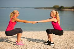 Ejercicio de dos mujeres en la playa que hace posiciones en cuclillas Imagen de archivo libre de regalías