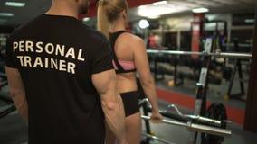 Ejercicio de elevación femenino joven de la barra del peso que hace bajo control de su instructor almacen de video